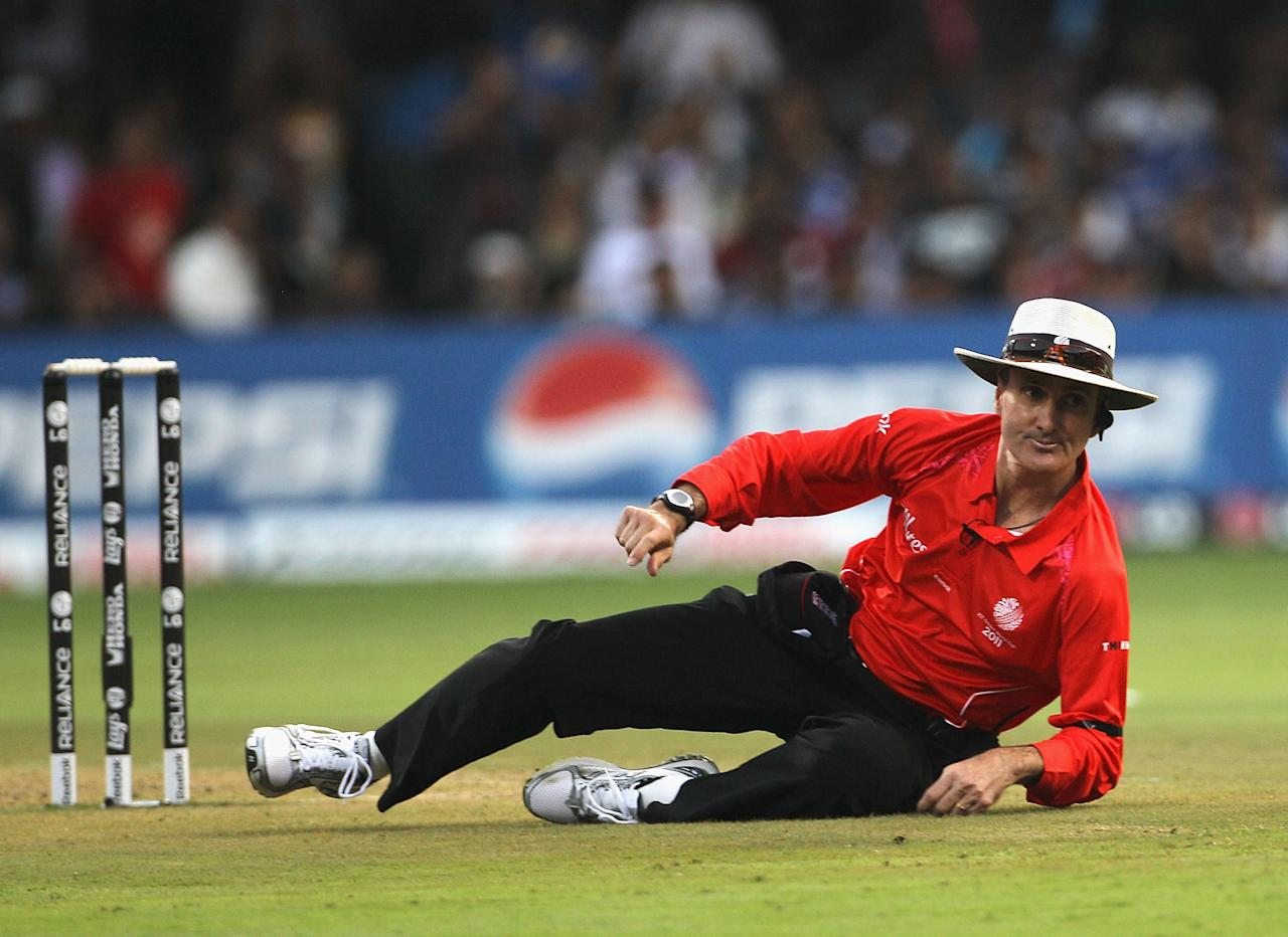 BANGALORE, INDIA - FEBRUARY 27:  Umpire Billy Bowden goes to ground avoiding a shot from MS Dhoni of India during the 2011 ICC World Cup Group B match between India and England at M. Chinnaswamy Stadium on February 27, 2011 in Bangalore, India.  (Photo by Hamish Blair/Getty Images)