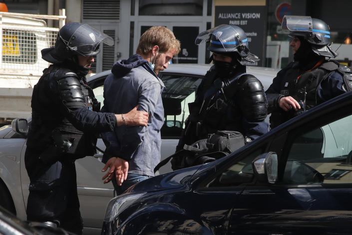 Police officers detain a demonstrator during a banned protest in support of Palestinians in the Gaza Strip, Saturday, May, 15, 2021 in Paris. Marches in support of Palestinians in the Gaza Strip were being held Saturday in a dozen French cities, but the focus was on Paris, where riot police got ready as organizers said they would defy a ban on the protest. (AP Photo/Michel Euler)