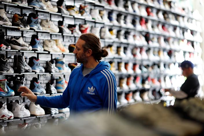 """Shoppers look at shoes for sale at CoolKicks. <span class=""""copyright"""">(Dania Maxwell / Los Angeles Times)</span>"""