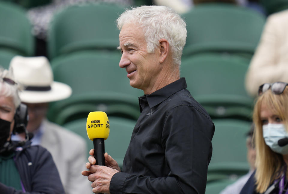 Former Wimbledon champion John McEnroe gives a TV interview ahead of the start of the men's singles final between Serbia's Novak Djokovic and Italy's Matteo Berrettini on day thirteen of the Wimbledon Tennis Championships in London, Sunday, July 11, 2021. (AP Photo/Kirsty Wigglesworth)