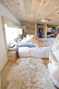 """<p>This serene tiny house in rural California is home to web designer Alek Lisefski, his girlfriend, Anjali, and their dog, Anya. Built on an 8- by 20-foot trailer, with three feet added for the back porch, the house features 10 windows and an all-glass door to opening up the <a href=""""http://tiny-project.com/completed-house-photos/"""" rel=""""nofollow noopener"""" target=""""_blank"""" data-ylk=""""slk:small interior space"""" class=""""link rapid-noclick-resp"""">small interior space</a> to the outdoors to feel less claustrophobic and more connected to the surroundings. Designed and built by Alek himself for about $30,000, he is now <a href=""""https://tiny-project.com/"""" rel=""""nofollow noopener"""" target=""""_blank"""" data-ylk=""""slk:selling construction plans"""" class=""""link rapid-noclick-resp"""">selling construction plans</a> so others can can build a house of their own to the same specs.</p><p><strong>RELATED: <a href=""""https://www.countryliving.com/home-maintenance/organization/advice/g104/small-space-decorating-0109/"""" rel=""""nofollow noopener"""" target=""""_blank"""" data-ylk=""""slk:Small-Space Decorating Ideas"""" class=""""link rapid-noclick-resp"""">Small-Space Decorating Ideas</a></strong></p>"""