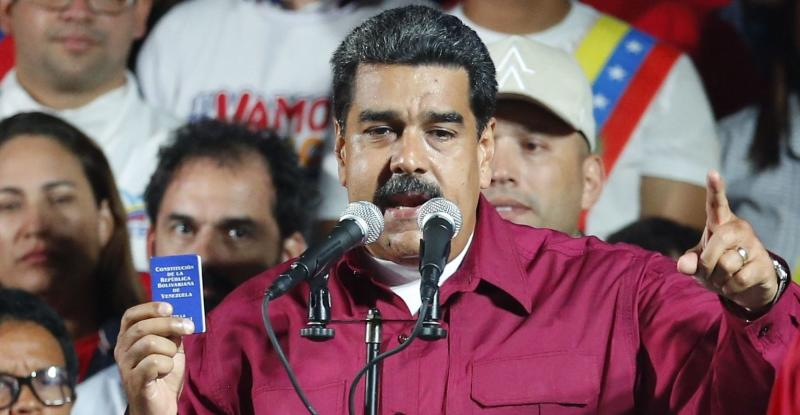 Venezuela's President Nicolas Maduro, holding a copy of the country's constitution, addresses supporters at the presidential palace in Caracas. (AP)
