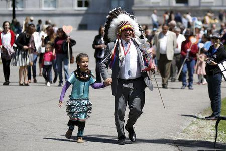 Assembly of First Nations National Chief Perry Bellegarde runs with a school girl to place a heart shaped card in the Heart Garden, which is meant to symbolize reconciliation, during the Truth and Reconciliation Commission of Canada closing ceremony at Rideau Hall in Ottawa June 3, 2015. REUTERS/Blair Gable