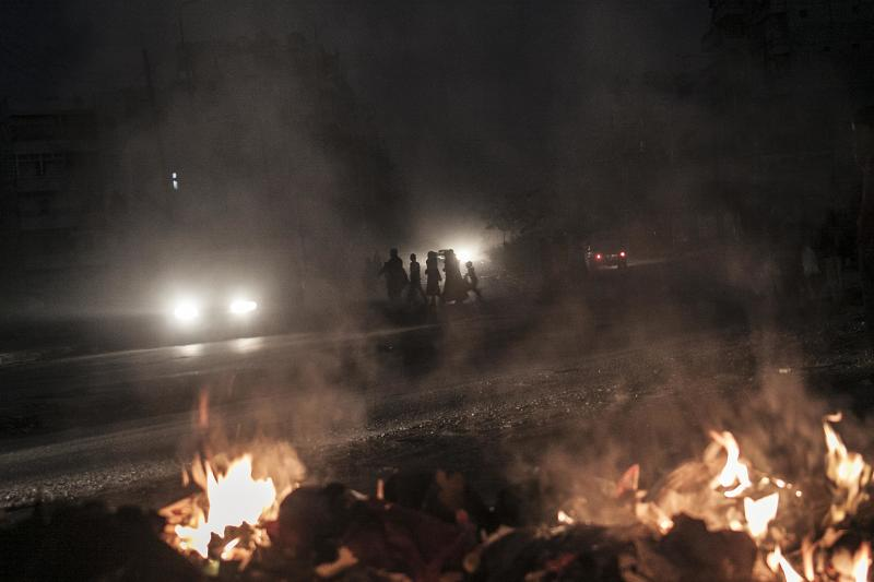 In this Saturday, Oct. 27, 2012 photo, Syrian residents cross a street as a pile of rubbish burns along the roadside in Aleppo, Syria. (AP Photo/Narciso Contreras).