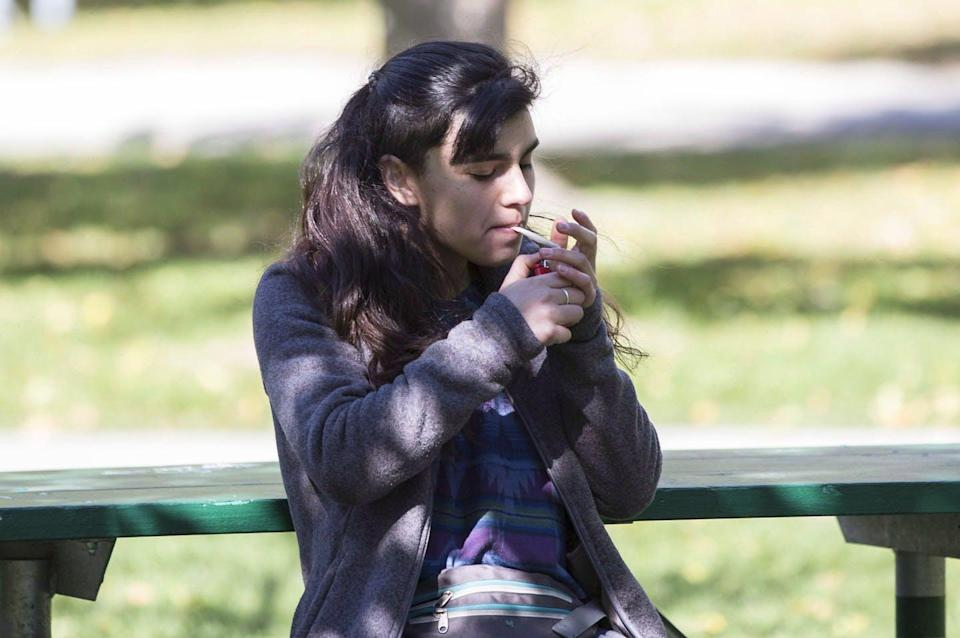 """<span class=""""caption"""">A woman marks the first day of legalization of cannabis across Canada as she lights a joint in a Toronto park in October 2018. </span> <span class=""""attribution""""><span class=""""source"""">THE CANADIAN PRESS/Chris Young </span></span>"""