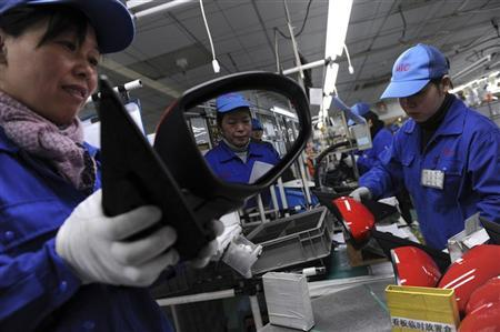 An employee is reflected on a rear view mirror at an assembly line of car components in Jiaxing