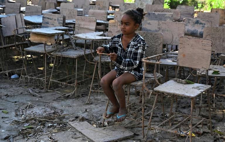 A little girl sits on a chair at a school that was destroyed by the Eta and Iota hurricanes