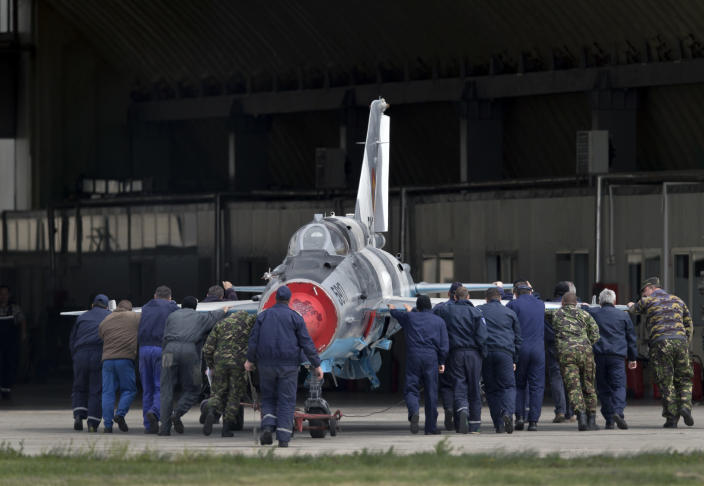 FILE - In this Thursday, April 10, 2014 file picture, Romanian air force employees push a MIG 21 Lancer fighter jet in Campia Turzii, Romania. The U.S. Air Force has deployed on Monday, Jan. 4, 2021, about 90 airmen and an unspecified number of drone aircraft to a base in central Romania, boosting its military presence in the region where there are allied concerns that Russia is trying to display its military strength. (AP Photo/Vadim Ghirda, File)