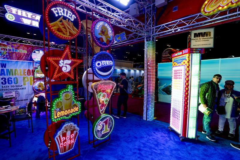 A vendor selling illuminated signs displays some of the available options during the International Association of Amusement Parks and Attractions convention Tuesday, Nov. 19, 2019, in Orlando, Fla. (AP Photo/John Raoux)