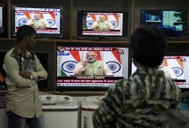 People watch Indian Prime Minister Narendra Modi addressing the nation, on television in Hyderabad, India, Saturday, Dec. 31, 2016. A day after the deadline for depositing old 500- and 1,000-rupee notes, Modi called the demonetization a purification drive during his Saturday speech. (AP Photo/Mahesh Kumar A.)