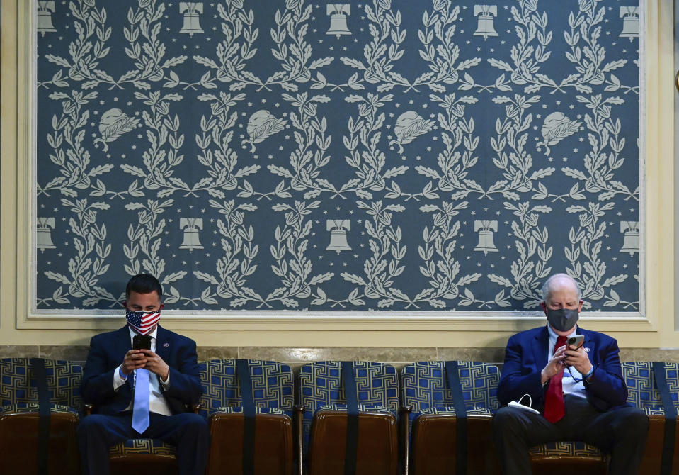 Two members of Congress look at their phones as they sit apart, socially distanced, ahead President Joe Biden's address to a joint session of Congress, Wednesday, April 28, 2021, in the House Chamber at the U.S. Capitol in Washington. (Jim Watson/Pool via AP)
