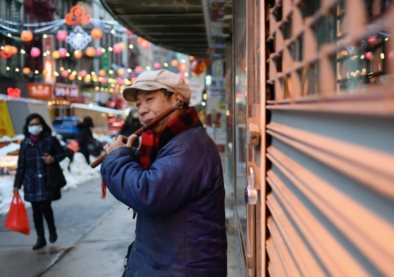 A man plays the flute as people walk through Chinatown in New York City on February 11, 2021