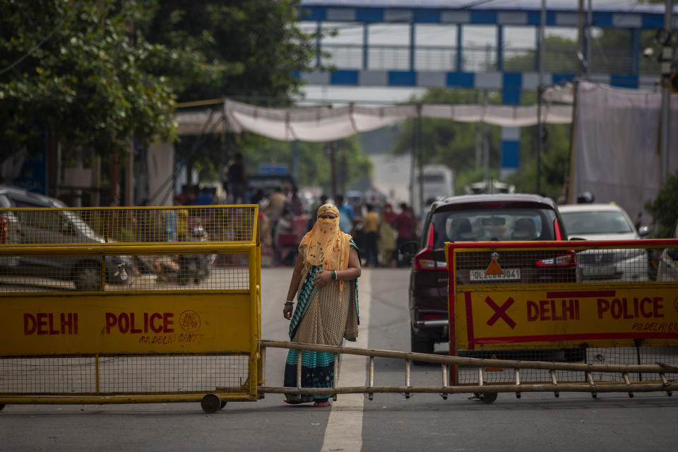 A woman stands on a road blocked by protesters at a demonstration site outside a crematorium where a 9-year-old girl from the lowest rung of India's caste system was, according to her parents and protesters, raped and killed earlier this week, in New Delhi, India, Thursday, Aug. 5, 2021. (AP Photo/Altaf Qadri)