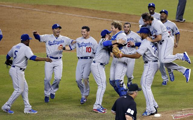 Los Angeles Dodgers celebrate after capturing the NL West title with a 7-6 win over the Arizona Diamondbacks in baseball game Thursday, Sept. 19, 2013, in Phoenix. (AP Photo/Ross D. Franklin)