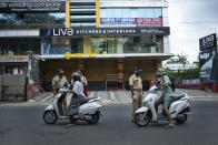 Policemen check the credentials of commuters during a lockdown imposed to curb the spread of coronavirus in Kochi, Kerala state, India, Saturday, May 8, 2021. Kerala, which emerged as a blueprint for tackling the pandemic last year, began a lockdown on Saturday. (AP Photo/R S Iyer)