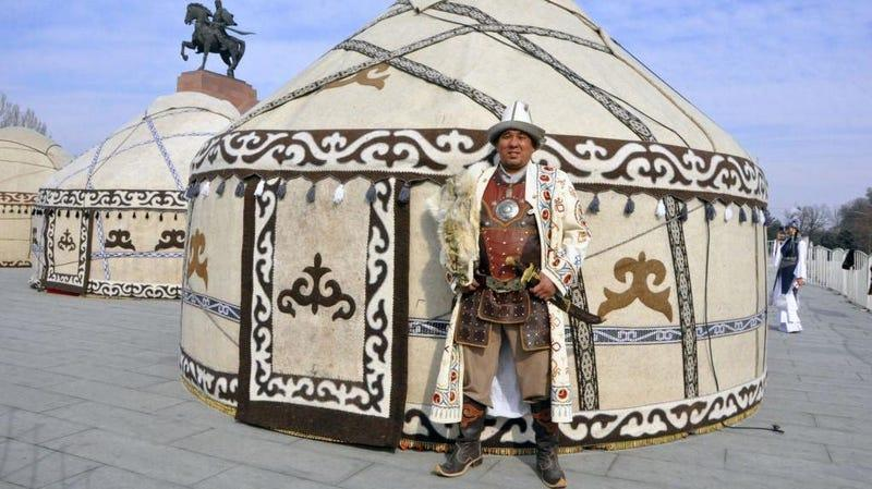 a man in ethnic costume in front of a yurt