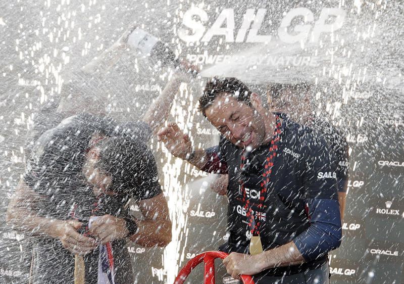 The British SailGP team spray champagne on their skipper Ben Ainslie as they celebrate winning the first leg of the series in Sydney, Saturday, Feb. 29, 2020. Britain beat Australia in the final match race. (AP Photo/Rick Rycroft)