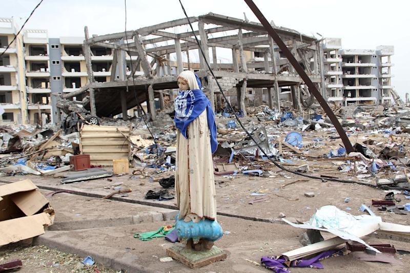 A statue of the Virgin Mary is all that remains of the St. Louis Catholic church, after a series of deadly explosions at a munitions depot devastated adjacent residential neighborhoods, killing at least 246 people, in Brazzaville, Republic of Congo Wednesday, March 7, 2012. Seen behind the statue are a new church building, center, and social housing, rear. Both were under construction at the time of the explosions. More than three days have passed since a catastrophic explosion laid waste to a section of the Republic of Congo's capital, and officials confirmed that as of Wednesday that no coordinated rescue effort had been launched, making it increasingly unlikely that any more people will be pulled alive from the flattened houses.(AP Photo)