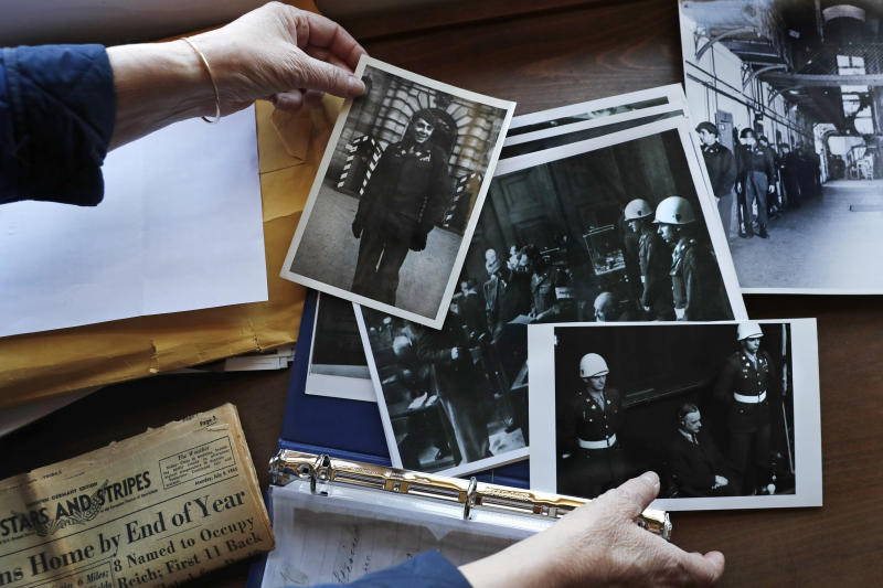 Emily DiPalma Aho looks over photographs and memorabilia of her father, Emilio DiPalma, a World War II veteran, at her home in Jaffrey, N.H., Wednesday, May 13, 2020. Emilio, who as a 19-year-old U.S. Army infantryman stood guard at the Nuremberg Nazi war crimes trials, died last month at the age of 93 after contracting the coronavirus at Holyoke Soldiers' Home in Massachusetts. (AP Photo/Charles Krupa)