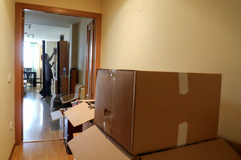 Ines Alcolea places objects at the dining room after unpacking moving boxes in her new rented apartment in Fuensalida