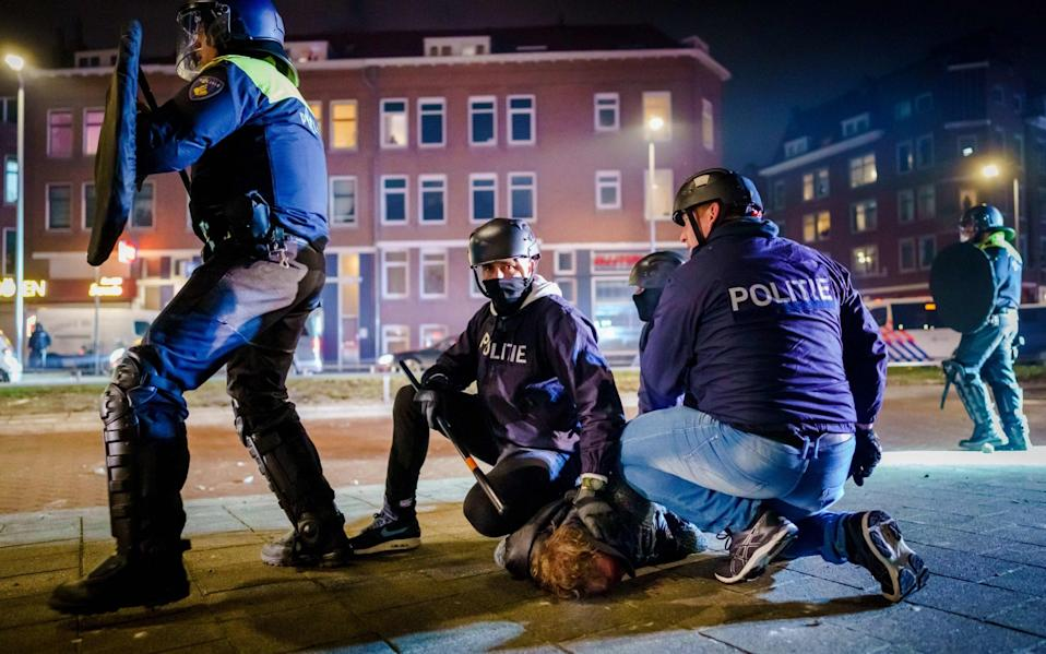 Dutch policemen arrest a man during clashes with a large group of young people on Beijerlandselaan in Rotterdam,