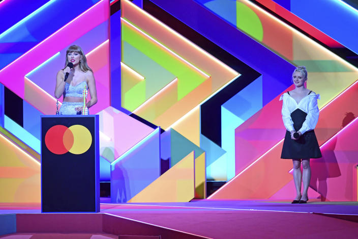Taylor Swift accepts the Global Icon award as Maisie Williams looks on during the Brit Awards 2021 at the O2 Arena, in London, Tuesday, May 11, 2021. (Ian West/PA via AP)