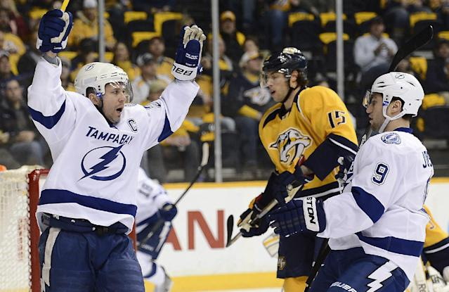 Tampa Bay Lightning right wing Martin St. Louis (26) celebrates with center Tyler Johnson (9) after St. Louis scored a goal against the Nashville Predators in the first period of an NHL hockey game, Thursday, Feb. 27, 2014, in Nashville, Tenn. Nashville Predators forward Craig Smith (15) looks on. (AP Photo/Mark Zaleski)