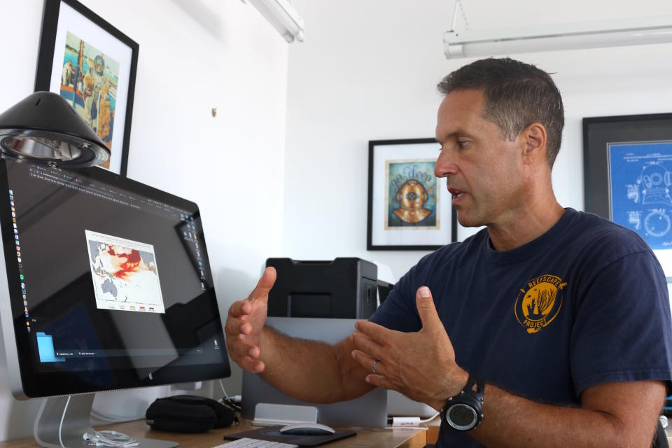 """In this Sept. 13, 2019 photo, ecologist Greg Asner, the director of Arizona State University's Center for Global Discovery and Conservation Science, reviews ocean temperature data at his lab on the west coast of the Big Island near Captain Cook, Hawaii. """"Nearly every species that we monitor has at least some bleaching,"""" said Asner after a dive in Papa Bay. (AP Photo/Caleb Jones)"""