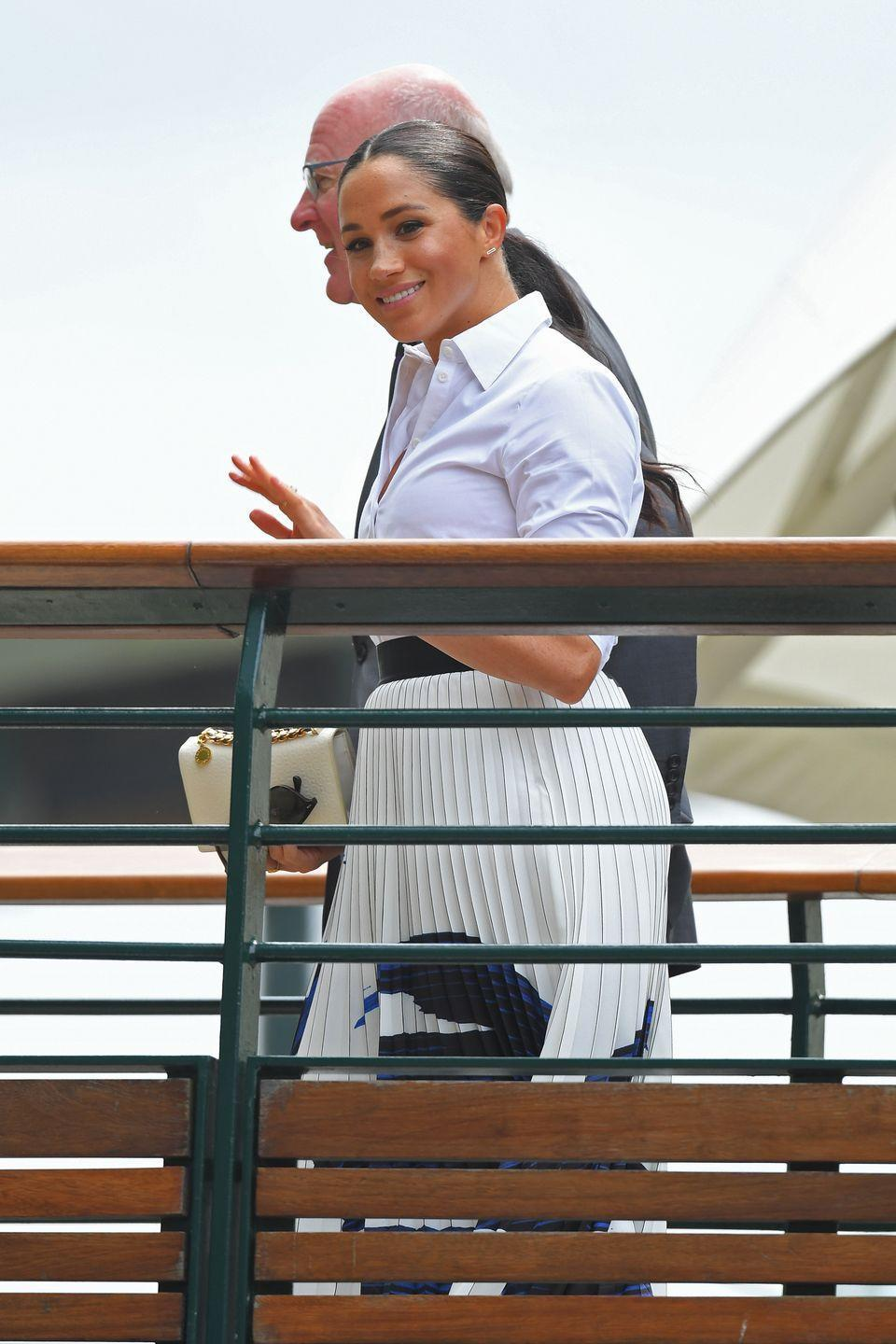 <p>The Duchess of Sussex arrived at Wimbledon in a crisp which collared shirt, which she paired with a blue and white pleated skirt. </p>