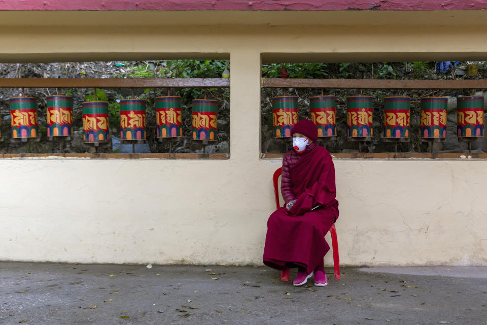 An exile Tibetan Buddhist nun wearing a mask as a precaution against the coronavirus waits to vote in Dharmsala, India, Sunday, Jan. 3, 2021. Exile Tibetans Sunday voted in the first round to elect a new political leader and members of the Tibetan parliament in exile. (AP Photo/Ashwini Bhatia)