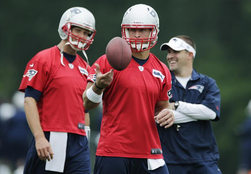 New England Patriots quarterback Tim Tebow, center, tosses the ball as Tom Brady, left, talks with offensive coordinator Josh McDaniels during a team football practice in Foxborough, Mass., Tuesday June 11, 2013. (AP Photo/Charles Krupa)