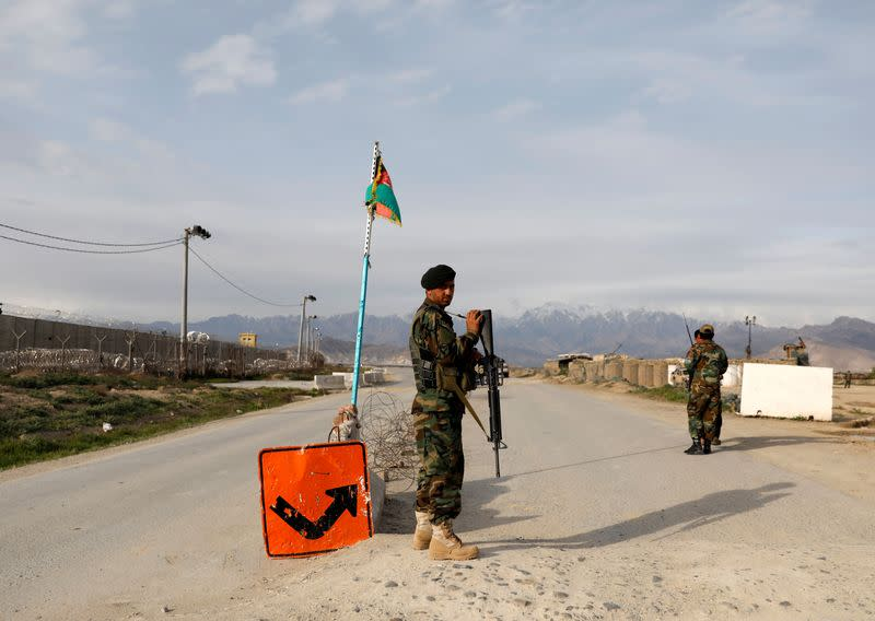 An Afghan National Army (ANA) soldier stands guard at a checkpoint outside Bagram prison, ahead of the release of 100 Taliban prisoners, north of Kabul