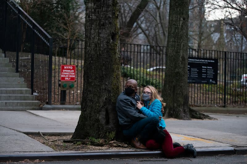 People wearing masks take cover while a man is shooting outside the Cathedral Church of St. John the Divine in Manhattan