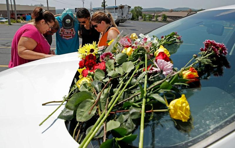 People pray next to a car believed to belong to a victim of a last night's duck boat accident, in Branson, Missouri