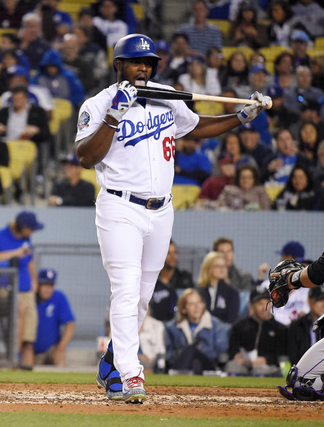 Los Angeles Dodgers' Yasiel Puig licks his bat after taking a strike during the fourth inning of the team's baseball game against the Colorado Rockies on Tuesday, May 22, 2018, in Los Angeles. (AP Photo/Mark J. Terrill)