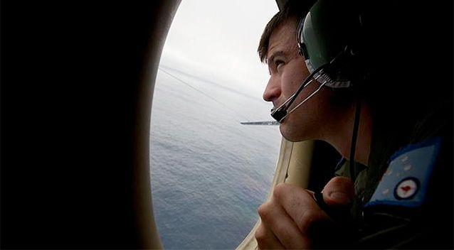 A crewm member of an RAAF AP-3C Orion aircraft looks out from an window during the search for potential MH370 debris. Photo: Getty.