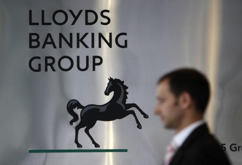 FILE PHOTO: A pedestrian passes the head office of the Lloyds Banking Group in London