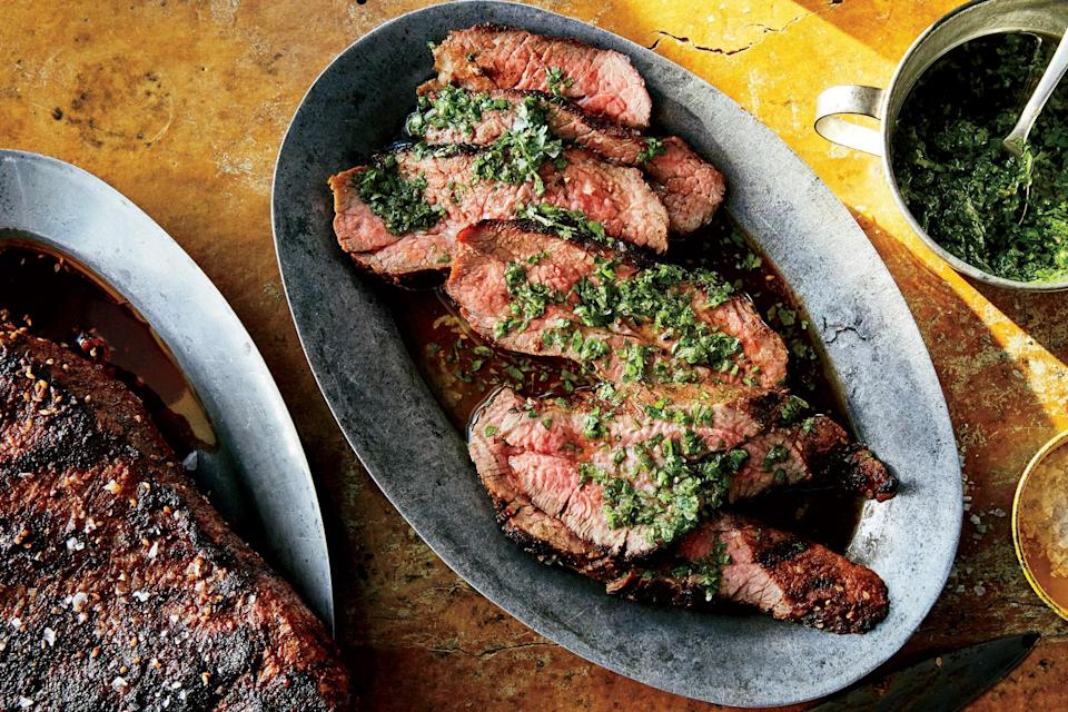 """This grilled steak recipe calls for tri-tip—a tender, triangular cut of beef tucked near the sirloin—but plain old sirloin steaks are great too. It won't taste plain, particularly with garlicky, herby chimichurri spooned on top. <a href=""""https://www.epicurious.com/recipes/food/views/tri-tip-with-chimichurri?mbid=synd_yahoo_rss"""" rel=""""nofollow noopener"""" target=""""_blank"""" data-ylk=""""slk:See recipe."""" class=""""link rapid-noclick-resp"""">See recipe.</a>"""