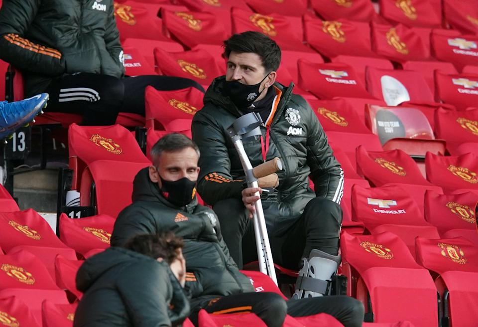 Harry Maguire watches on from the stands at Old Trafford (Reuters)