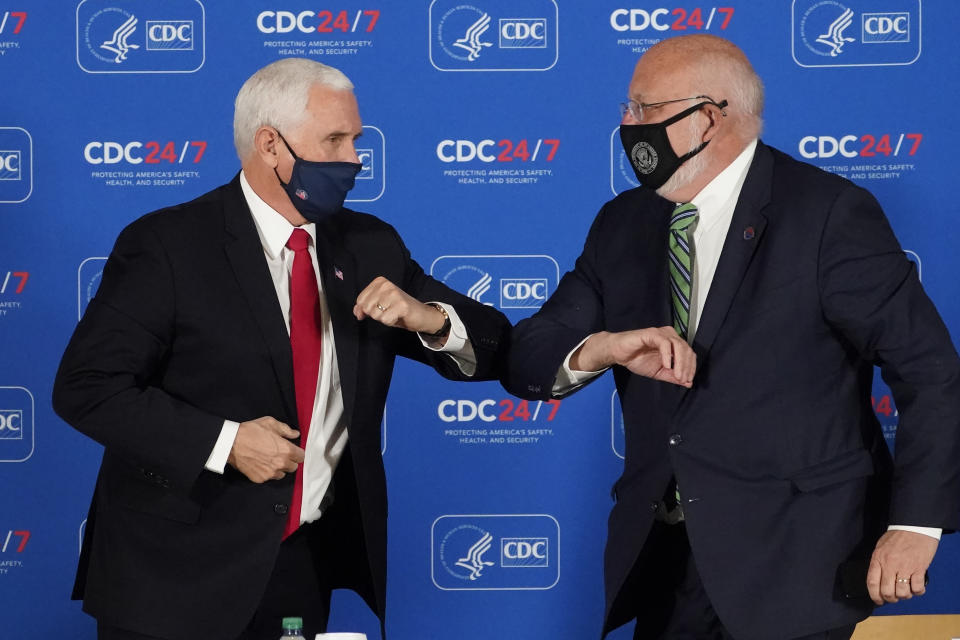 Vice President Mike Pence, left, and Centers for Disease Control and Prevention director Dr. Robert Redfield exchange elbow bumps after a briefing at the CDC Friday, Dec. 4, 2020, in Atlanta. (AP Photo/John Bazemore)