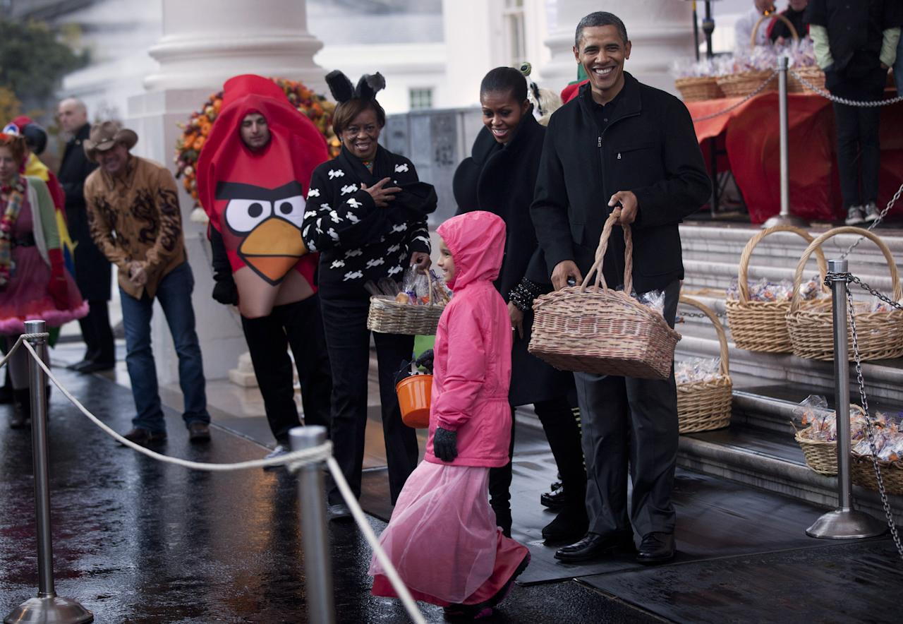WASHINGTON - OCTOBER 29:  U.S. President Barack Obama, first lady Michelle Obama and her mother Marian Robinson greet trick or treaters at the White House October 29, 2011 in Washington, DC.  President Barack Obama and first lady Michelle Obama hosted military families and other trick or treaters for a Halloween party.  (Photo by Brendan Smialowski/Getty Images)