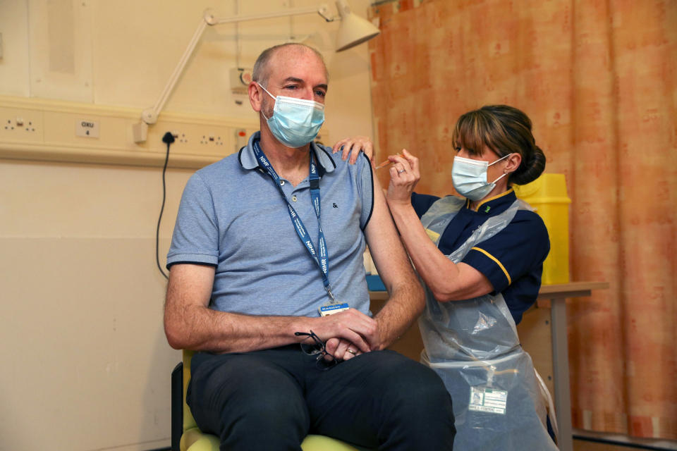 Professor Andrew Pollard, Director of the Oxford Vaccine Group, and a professor of paediatric infection and immunity receives the Oxford University/AstraZeneca COVID-19 vaccine from nurse Sam Foster, at the Churchill Hospital in Oxford, England, Monday, Jan. 4, 2021. England's National Health Service says a retired maintenance manager has received the first injection of the new vaccine developed by Oxford University and drug giant AstraZeneca. Dialysis patient Brian Pinker became the very first person to be vaccinated by the chief nurse at Oxford University Hospital. (Steve Parsons/Pool Photo via AP)