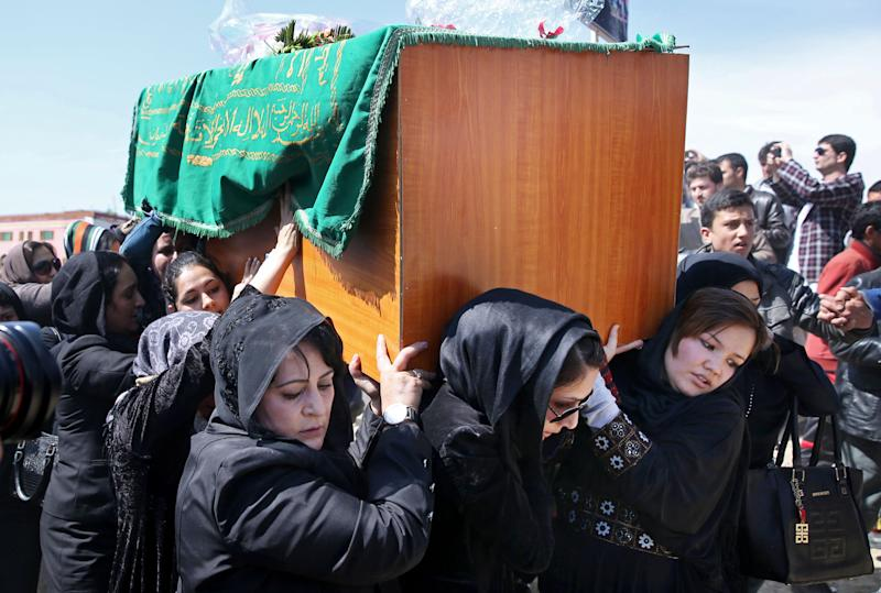 FILE - In this Sunday, March 22, 2015 file photo, Afghan women rights activists carry the coffin of 27-year-old Farkhunda, an Afghan woman who was beaten to death by a mob, during her funeral, in Kabul, Afghanistan. Hundreds of people gathered in northern Kabul for the funeral of Farkhunda, who like many Afghans is known by only one name. She was killed late Thursday by a mob of mostly men who beat her, set her body on fire and then threw it into the Kabul River, according to police accounts. Police are still investigating what prompted the mob assault. (AP Photo/Massoud Hossaini, File)