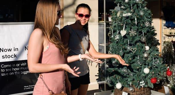young females wearing summer clothes on hot sunny day bemused at early christmas shop window display