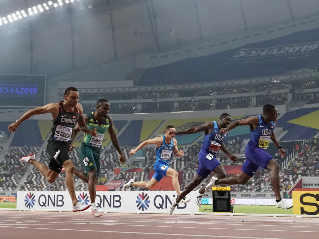 Christian Coleman, of the United States, crosses the finish line to win the men's 100 meter final ahead of silver medalist Justin Gatlin, also of the United States, during the World Athletics Championships in Doha, Qatar, Saturday, Sept. 28, 2019. Andre De Grasse, of Canada, won the bronze medal. (AP Photo/David J. Phillip)