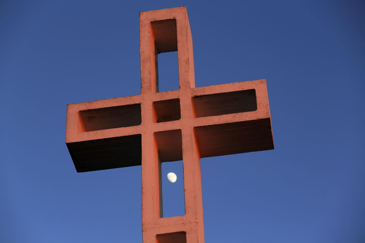 The moon is shown between the massive cross sitting atop the Mt. Soledad War Memorial in La Jolla, California on December 12, 2013. A federal judge has ruled that the cross is an unconstitutional religious display on government land and must come down within 90 days. The decision could result in the case being sent back to the U.S. Supreme Court. REUTERS/Sandy Huffaker (UNITED STATES - Tags: SOCIETY RELIGION POLITICS)