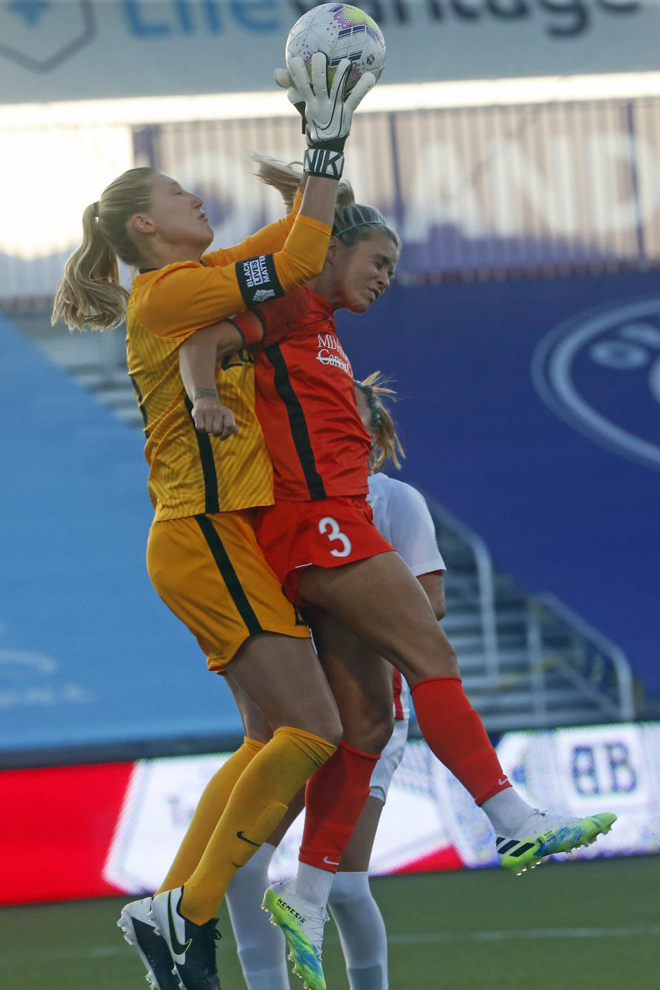 OL Reign goalkeeper Casey Murphy, left, makes a save as Houston Dash forward Rachel Daly (3) goes up during the first half of an NWSL Challenge Cup soccer match at Zions Bank Stadium, Saturday, July 4, 2020, Herriman, Utah. (AP Photo/Rick Bowmer)