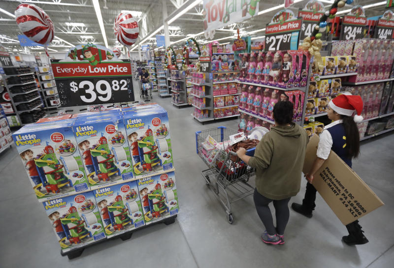 In this Wednesday, Oct. 26, 2016, file photo, a shopper, left, walks with a store associate in the toy section at Walmart in Teterboro, N.J. (AP Photo/Julio Cortez, File)