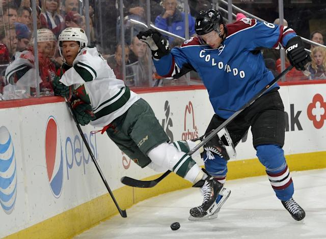 Minnesota Wild right wing Jason Pominville, left, is slammed into the boards by Colorado Avalanche defenseman Erik Johnson (6) during the second period of an NHL hockey game on Saturday, Nov. 30, 2013, in Denver. (AP Photo/Jack Dempsey)