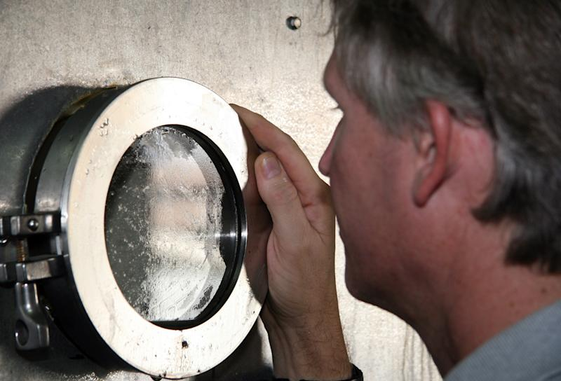 This Aug. 8, 2012, shows Peter Fix, a conservator, peers through a tiny window on a 40-foot-long, 8-feet-wide freeze dryer at the Texas A&M University Center for Maritime Archaeology and Conservation in Bryan, Texas. Researchers are using the gigantic freeze-dryer to remove moisture from the wreckage of a 17th-century French ship used by famed explorer La Salle and sank more than 300 years ago off the Texas coast.  The vessel will become the centerpiece at a state history museum in Austin. (AP Photo/Michael Graczyk)